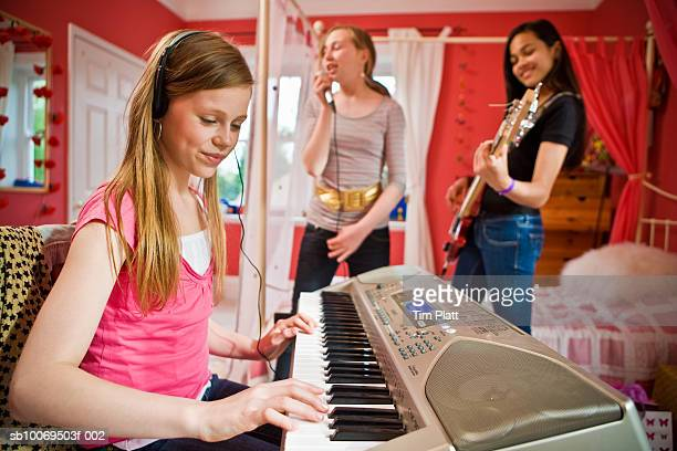Girls (12-13) playing music in bedroom
