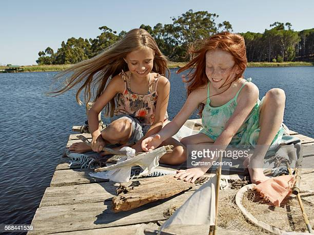 2 girls playing on a jetty at a lake