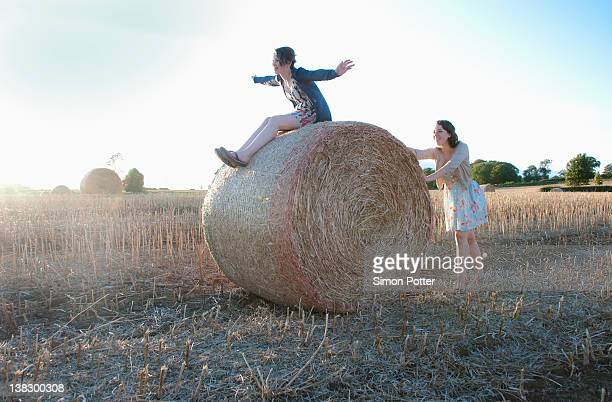 Girls playing on hay bale in field