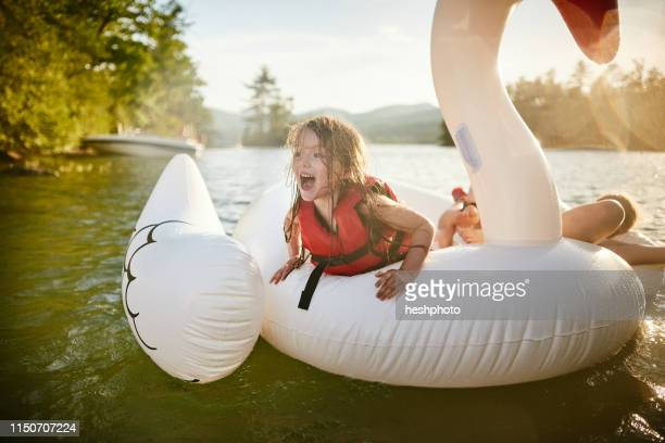 girls playing on inflatable swan in lake - heshphoto fotografías e imágenes de stock