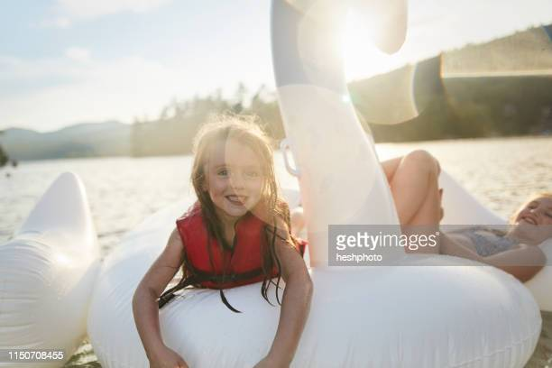girls playing on inflatable swan in lake - heshphoto stock pictures, royalty-free photos & images