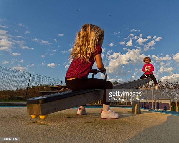 girls playing on see-saw - s0ulsurfing stock pictures, royalty-free photos & images
