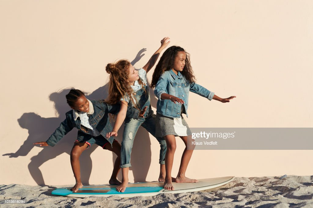 Girls playing on surfboard on the beach, on studio backdrop : Stock Photo
