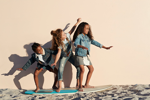 Girls playing on surfboard on the beach, on studio backdrop - gettyimageskorea