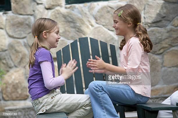 Girls (8-9) playing pattycake, smiling, side view
