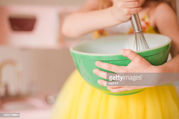 A girls playing pretend in her kitchen