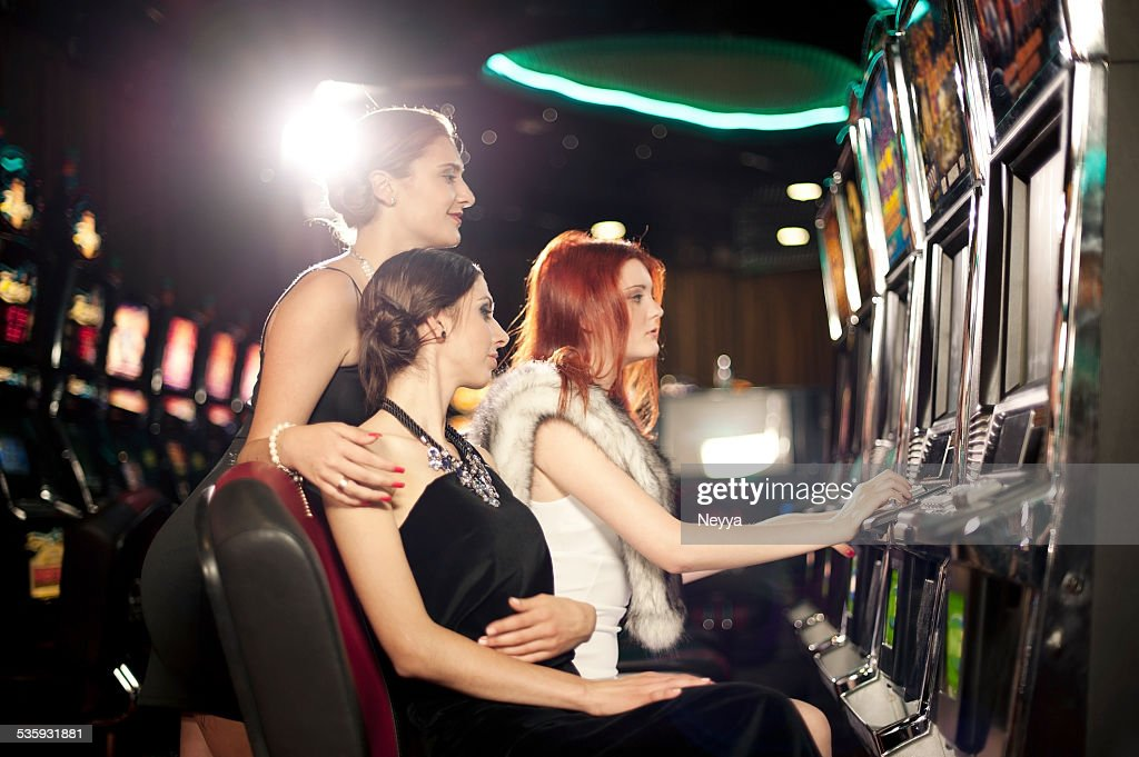 Girls playing slot machine in the casino : Stock Photo