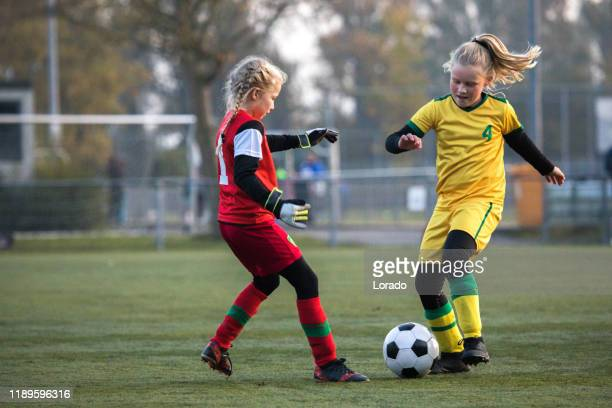 girls playing soccer during a football match - club football stock pictures, royalty-free photos & images