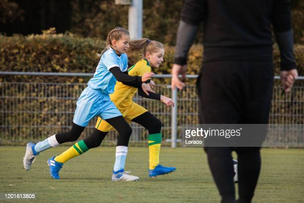 girls playing soccer during an evening football match - images foto e immagini stock