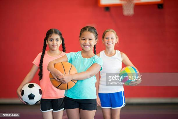 girls playing sports - tee sports equipment stock photos and pictures