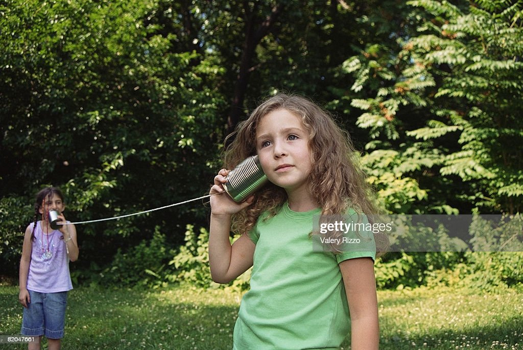 Girls playing telephone with cans and string : Stock Photo