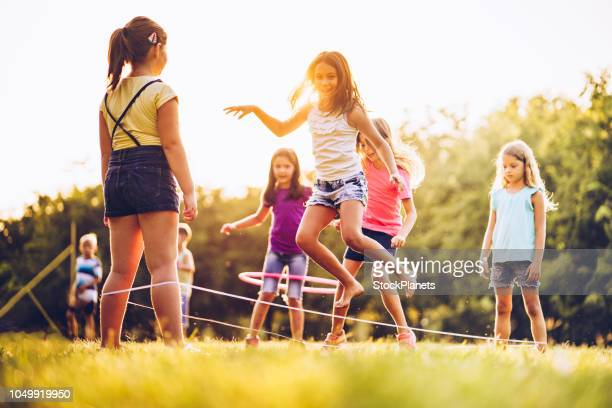 girls playing together at sunset - skipping along stock pictures, royalty-free photos & images