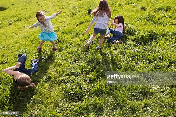 girls playing together in field - gras stock pictures, royalty-free photos & images