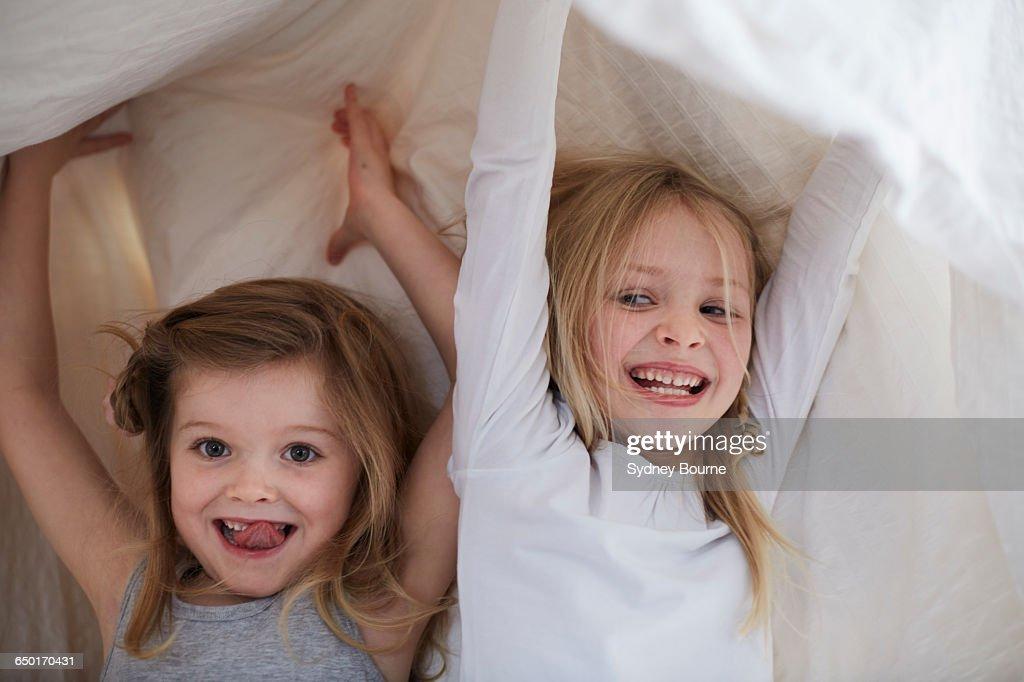 Girls playing under blanket : Stock Photo