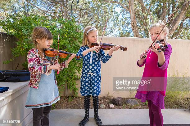 Girls playing violin outdoors