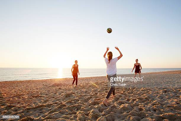 girls playing volleyball at the beach - beachvolleybal stockfoto's en -beelden