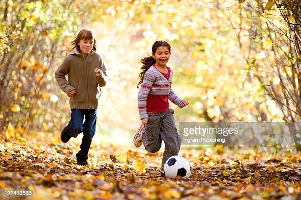Girls playing with a soccer ball in a park