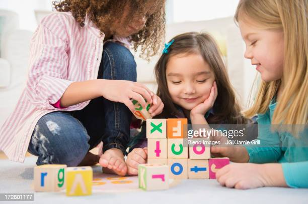 Girls playing with colorful blocks in living room