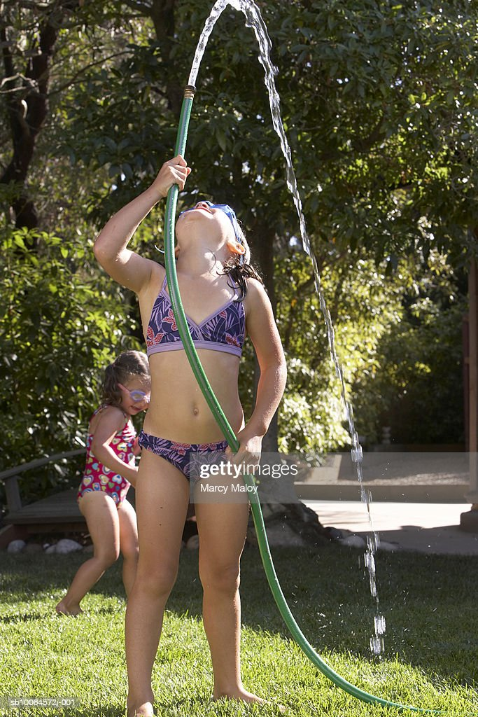 Girls (2-3, 6-7) playing with hose in yard : Stock Photo