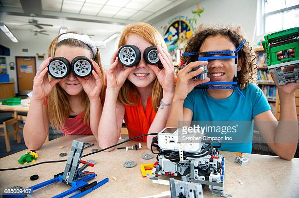 Girls playing with plastic blocks and wheels in library