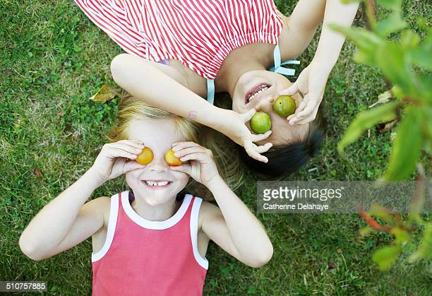 2 girls playing with plums in a garden