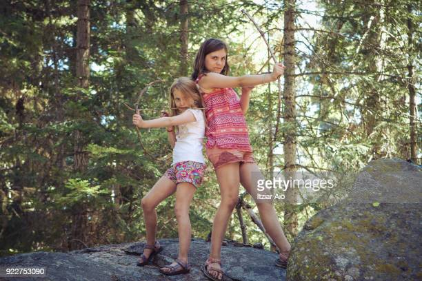 girls playing with self-made archery bows - wilderness stock photos and pictures