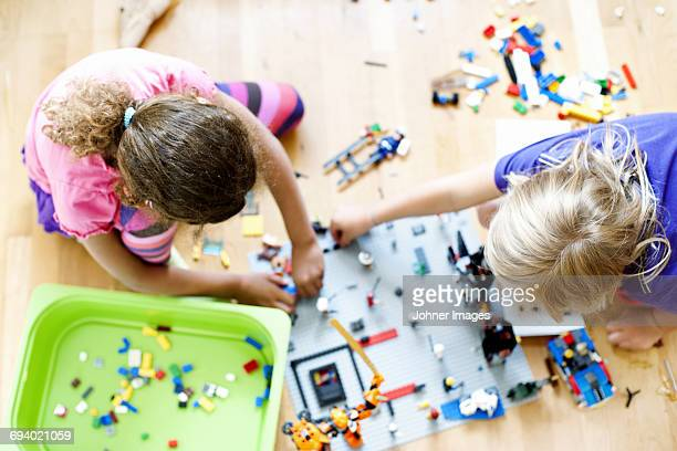 Girls playing with toy blocks on floor