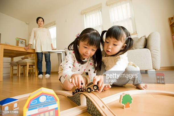 Girls playing with toy trains at home