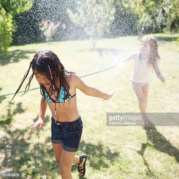 2 girls playing with water in a garden - petite fille culotte photos et images de collection
