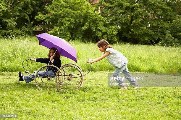 girls playing with wheeled vehicle - geval stockfoto's en -beelden