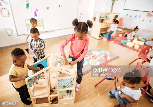 girls playing with wooden blocks creating a new building - preschool age stock pictures, royalty-free photos & images