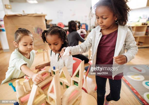 Girls playing with wooden blocks creating a new building