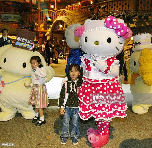Girls pose for a photograph with popular cartoon characters including Hello Kitty at the Sanrio Puroland in Tokyo 01 November 2004 Hello Kitty...