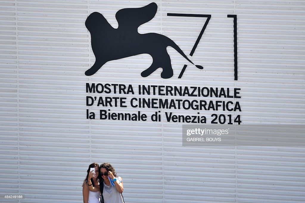 Girls pose for a selfie on the opening day of the 71st Venice Film Festival on August 27, 2014 at Venice Lido.