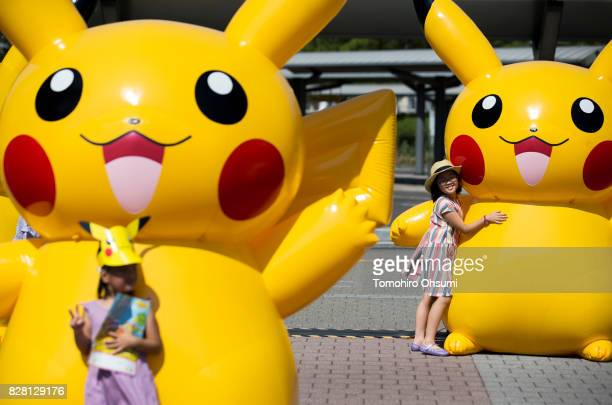 Girls pose for photographs with balloons of Pikachu a character from Pokemon series game titles during the Pikachu Outbreak event hosted by The...