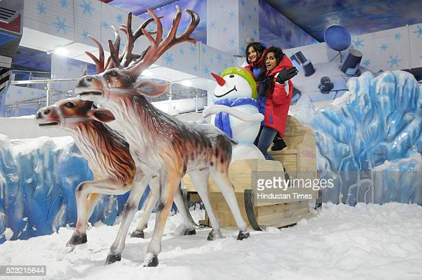 Girls pose with dummy Reindeer Sleigh at Ski India the indoor SciFi themed Snow Park during its launch at DLF Mall of India on April 22 2016 in Noida...