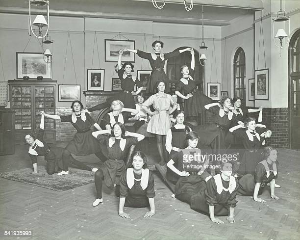 Girls posed in tableaux Sandhurst Road Evening Institute London 1914 Posed on and around a gynmastic horse Artist unknown