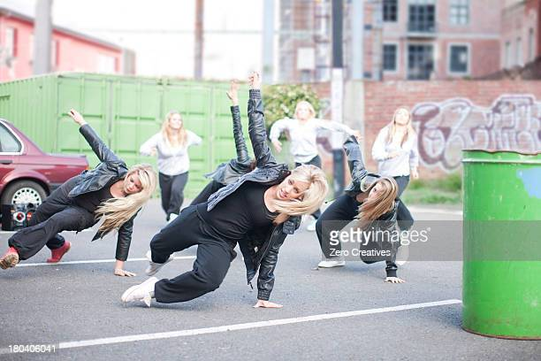 Girls practicing dance moves in carpark