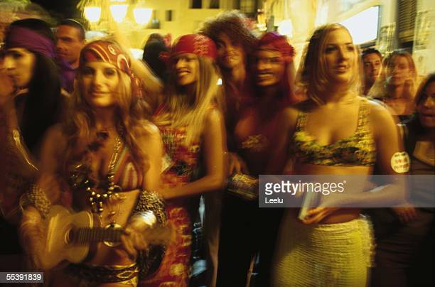 Girls promoting a flower power night at Pacha wearing hippy style clothing during a street parade Ibiza Town July 2000