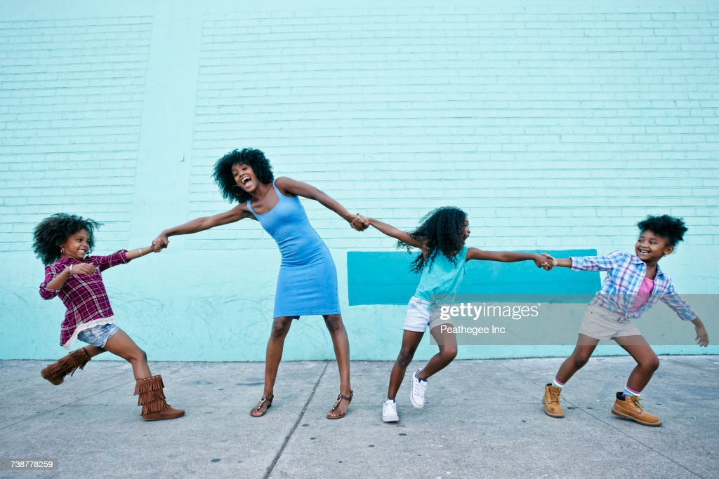 Girls pulling arms of woman in opposite directions : Foto de stock