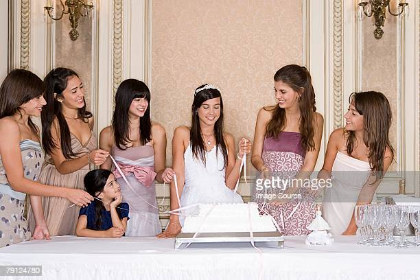 girls pulling ribbons from cake - quinceanera stock pictures, royalty-free photos & images