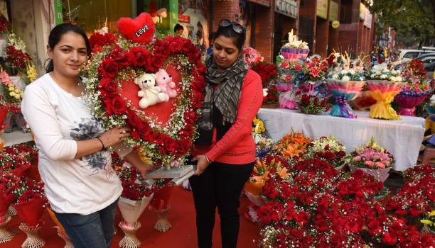 Girls purchasing flowers on the eve of Valentine's Day from a shop at sector 35 market on February 13 2017 in Chandigarh India