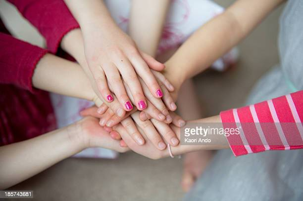 girls putting hands together,  close up - cobham surrey stock pictures, royalty-free photos & images