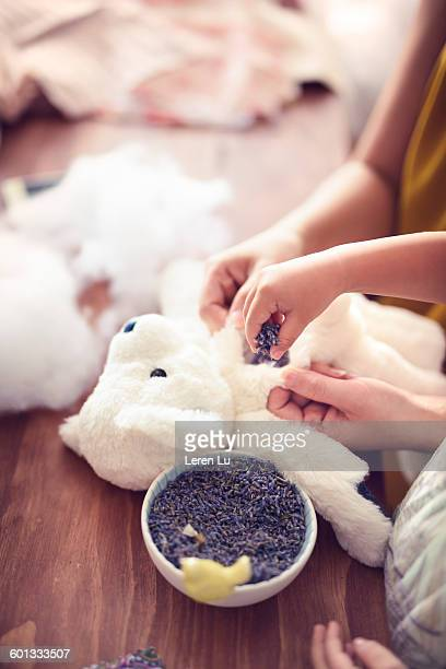 Girls putting lavender into stuffed doll