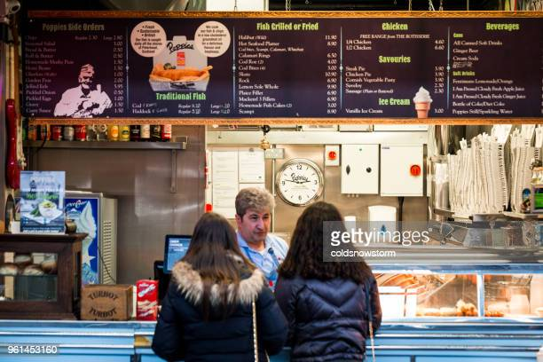 girls queuing at fish and chips counter, london, uk - fast food restaurant stock pictures, royalty-free photos & images