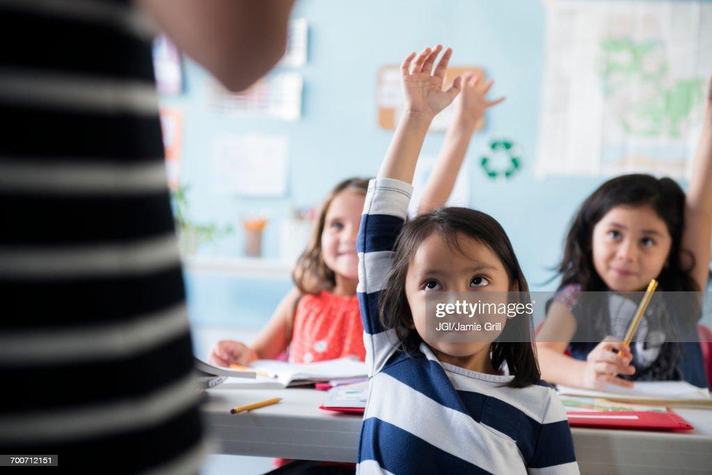 Girls raising hand for teacher in classroom : Foto de stock