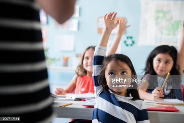 girls raising hand for teacher in classroom - criança de escola fundamental - fotografias e filmes do acervo