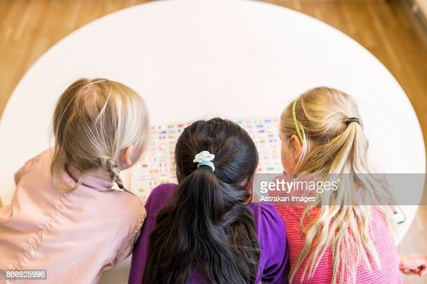 Girls (8-9) reading book together