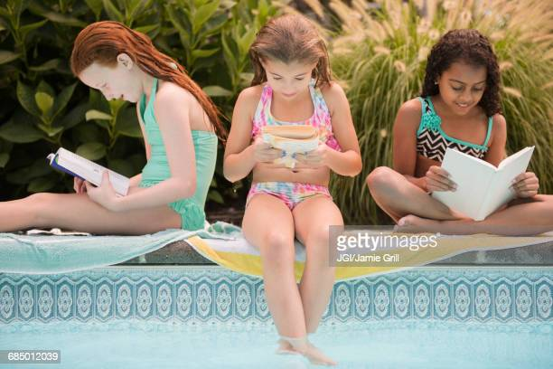 Girls reading books at the edge of swimming pool