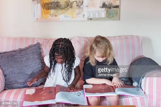 Girls reading childrens books on sofa
